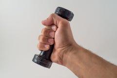 Männliche Hand, die ein schwarzes Dumbell hält. Sport stockfotografie