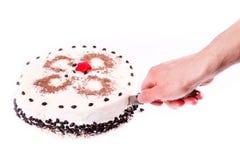 Männliche Hand, die ein Stück des geschmackvollen Kaffeeschokoladenkuchens schneidet Lizenzfreie Stockbilder