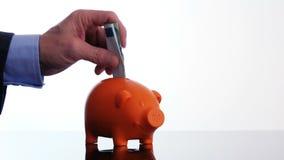 Männliche Hand, die eine Eurorechnung in ein Sparschwein einsetzt stock video footage