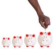 Männliche Hand, die eine Münze in ein Sparschwein setzt Stockbilder