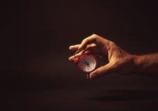 Männliche Hand, die eine rote Uhr hält Lizenzfreie Stockfotos