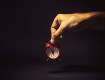 Männliche Hand, die eine rote Uhr hält Lizenzfreie Stockfotografie