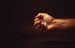 Männliche Hand, die eine rote Uhr hält Stockbild