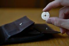 Männliche Hand, die eine silberne norwegische Münzenwährung in Norwegen, norwegische Krone, NOK hält Lizenzfreie Stockbilder