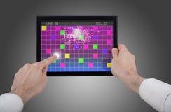 Männliche Hand, die einen Berührungsflächen-PC spielt Spiel anhält Stockfotografie