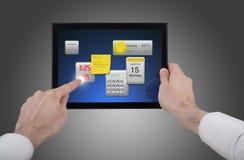 Männliche Hand, die einen Berührungsflächen-PC unter Verwendung der Programme anhält Stockbild