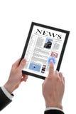 Männliche Hand, die einen Berührungsflächen-PC zeigt Zeitung anhält Stockbilder