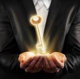 Männliche Hand, die einen goldenen Schlüssel hält Lizenzfreie Stockfotografie