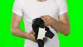 Männliche Hand, die einen Kopfhörer der virtuellen Realität nimmt Grüner Bildschirm Langsame Bewegung stock video footage