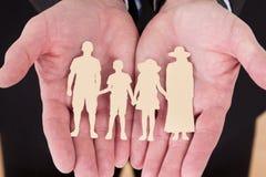 Männliche Hand, die Familien-Ausschnitt-Form hält Stockfoto