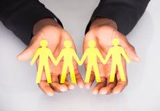 Männliche Hand, die Familien-Ausschnitt-Form hält Lizenzfreie Stockbilder