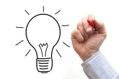 Männliche Hand, die Glühlampe über einem weißen Hintergrund zeichnet Lizenzfreie Stockfotografie