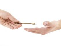 Männliche Hand, die goldenen Schlüssel hält stockfotografie