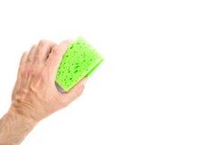 Männliche Hand, die grünen Reinigungs-Schwamm auf weißem Hintergrund hält Stockfotos