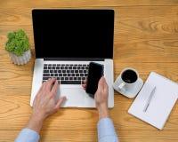 Männliche Hand, die Handy bei der Anwendung der Laptop-Computers hält Lizenzfreies Stockbild