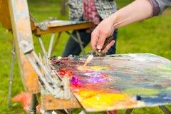 Männliche Hand, die helle Farben mit einem paletteknife mischt Lizenzfreies Stockfoto