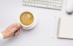 Männliche Hand, die Kaffeetasse Lattekunst auf weißer moderner Funktionstabelle hält stockbild