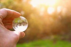 männliche Hand, die kleine Kristallkugel hält Reise und globales Fragekonzept Stockbilder