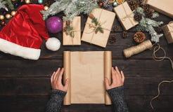 Männliche Hand, die leeres Papier mit Weihnachtsartikeln hält Stockfoto