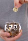 Männliche Hand, die Münze in eine piggy Querneigung setzt Stockfoto