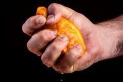 Männliche Hand, die Orange zusammendrückt lizenzfreie stockbilder