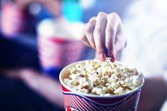 Männliche Hand, die Popcorn vom Kasten im Kino nimmt Lizenzfreie Stockfotos