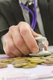 Halten des Stethoskops auf Eurogeld Stockfotografie