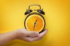 Männliche Hand, die Wecker der orange Frucht auf gelbem Backgrou hält Stockbild