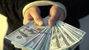 Männliche Hand gesprungen mit dem Seilholdingstapel von amerikanischen Dollarbanknoten des Geldes, Finanz-rectrictions Konzept stock footage
