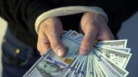 Männliche Hand gesprungen mit dem Seilholdingstapel von amerikanischen Dollarbanknoten des Geldes, Finanz-rectrictions Konzept stock video footage