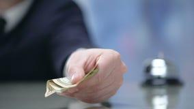 Männliche Hand gibt Geld an der Hotelaufnahme und zahlt für Geschäftsreiseanpassung stock footage