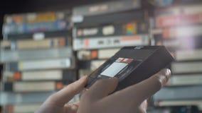 Männliche Hand hebt eine VHS-Kassette vom Regal auf stock video footage
