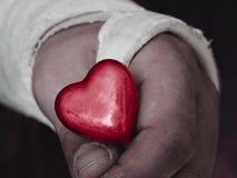 Männliche Hand im Gipsabdruck, der kleines glattes rotes Herz hält lizenzfreies stockfoto