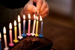 Männliche Hand ist Blitz herauf einige bunte Kerzen Stockfotos