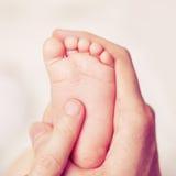 Männliche Hand mit Babyfüßen Stockfoto