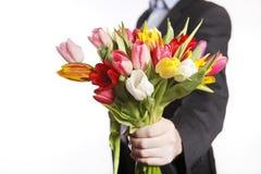 Männliche Hand mit dem Blumenstrauß von Tulpen, lokalisiert Stockbilder