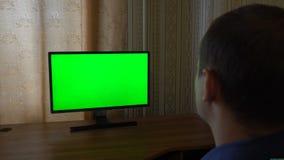 Männliche Hand mit Fernsehfernschalten-Kanälen auf einem grünen Schirm Fernsehgesichtspunkt stock video