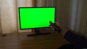 Männliche Hand mit Fernsehfernschalten-Kanälen auf einem grünen Schirm Fernsehgesichtspunkt stock video footage