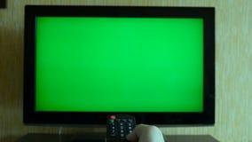 Männliche Hand mit Fernsehfernschaltenkanälen auf grünem Schirm Fernsehgesichtspunkt stock video
