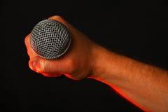 Männliche Hand mit Mikrofon und rotem Licht auf Schwarzem Stockfotos