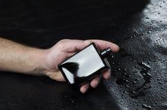 Männliche Hand mit modernem schwarzem männlichem Duft gegen ledernen Hintergrund Modell des Parfüms lizenzfreies stockfoto