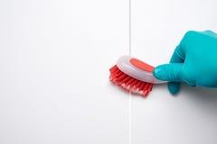 Männliche Hand mit roter Bürstenreinigung die Badezimmerfliesen und -abstände vor und nach Effekt Stockfotos