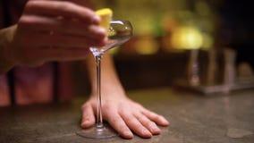 Männliche Hand reibt hohes Glas mit einer Scheibe der Orange im modernen Caféabschluß oben stock footage