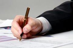 Männliche Hand schreibt in das Dokument Stockfotografie