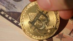 Männliche Hand setzt Bitcoin auf einen Stapel des Dollars stock footage