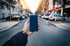 Männliche Hand unter Verwendung des intelligenten Telefons auf der Straße Konzept der Technologie und des Sozialen Netzes Geschäf lizenzfreie stockfotografie