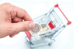 Männliche Hand wirft eine Münze in Geldkasten der Form der Laufkatze Lizenzfreie Stockfotos