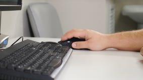 Männliche Handklickende Computermaus mit schwarzer Tastatur nahe Im zahnmedizinischen Röntgenbildkabinett Stift, Uhr, Notizbuch A stock video