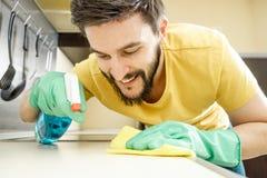 Männliche Hausmeisterreinigungsküche mit Schwamm Lizenzfreie Stockbilder