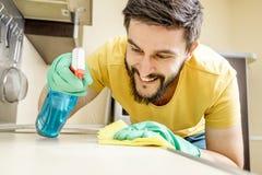 Männliche Hausmeisterreinigungsküche mit Schwamm Stockfotografie